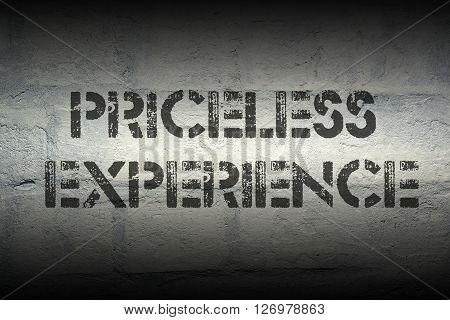 priceless experience stencil print on the grunge white brick wall