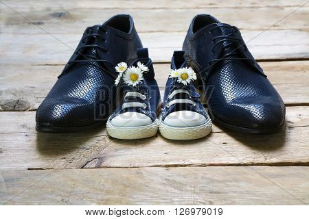 father's day kids sneakers with a bouquet of daisies standing between daddy's black men shoes on rustic gray wood copy space