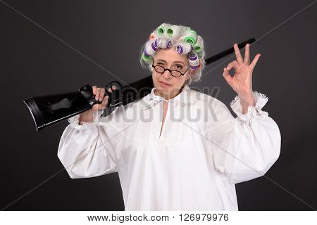Grandmother holding rifle and showing okay sign in studio over grey background. Happy elderly in glasses defending her residence.