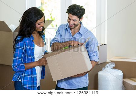 Young couple unpacking carton boxes in their new house