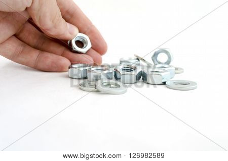 Several metal screw washers and nuts in human hand isolated on white background.