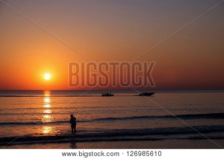 Sunset view at the beach with silhouette people relaxing