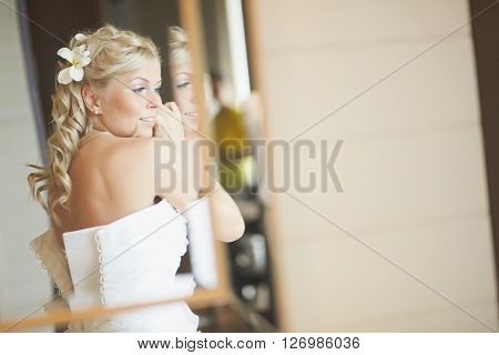 Gorgerous bride standing in front of mirror and fixing her hair and make up. Putting earings powdering and smilling. Wedding preparation in hotel room.