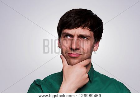 Portrait European thinking man in a green shirt on a neutral gray background. Emotion reflects the thinking process. Man look up to the left eyes narrowed chin hand props