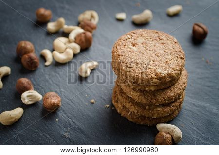 Whole grain cereal shortbread biscuits cookies stacked on black slate with cashew and hazel nuts. Selective focus on front of top cookie.
