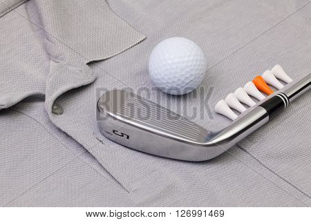 Detail of grey polo shirt and golf equipments