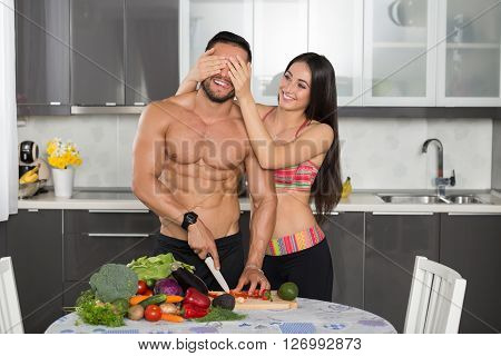 young fit couple in the kitchen cooking cutting vegetables having fun