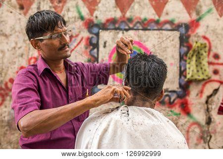 Mumbai, India - February 28, 2016: Roadside barber shop downtown in Mumbai, Maharashtra State, India.