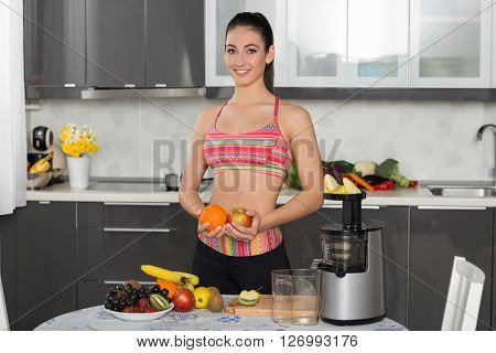 young fit woman in the kitchen holding an orange and an apple preparing juice