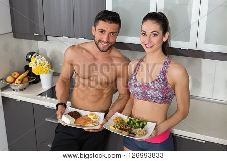 fit couple in the kitchen; animal versus plant proteins: one plate with beef eggs salmon cheese and chicken grill and another with nuts mushrooms broccoli lentil hummus and quinoa