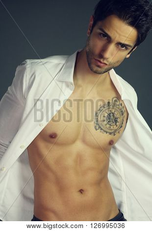Sensual man with open shirt over a gray background