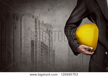 Hand Or Arm Of Engineer Hold Yellow Plastic Helmet For Worker