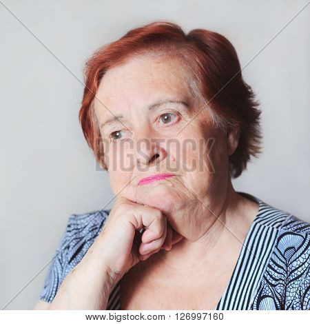 Sad senior woman sitting in room over white. Looking away. Contamplation.