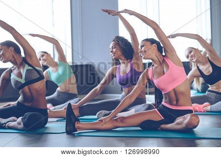Working over their dream bodies. Young beautiful young women with perfect bodies in sportswear doing stretching with smile at gym