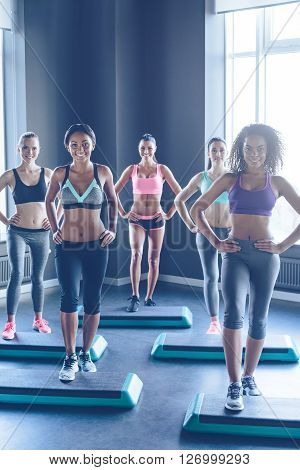 One more step for healthy body. Young beautiful women in sportswear with perfect bodies doing aerobics and looking at camera with smile at gym