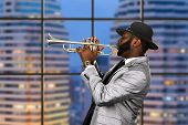 Afro trumpeter in black hat. Trumpet performance on skyscraper background. Reggae music for your pleasure. Classy musician on stage. poster