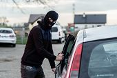 Man dressed in black with a balaclava on his head entering the vehicle and stealing a car. Car thief car theft concept poster