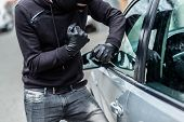 The man dressed in black with a balaclava on his head trying to break into the car. He uses a screwdriver. Car thief car theft concept poster
