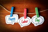 Paper speech bubbles with text Happy Labor Day hanging on the line against dark wooden background. poster