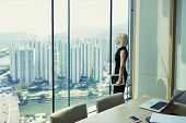 Blonde woman proud CEO is holding touch pad and looking in office window with cityscape while is standing in conference room near table with open laptop computer during her business trip in Hong Kong poster