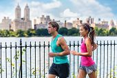 Running couple runners jogging in Central Park, NYC living healthy fitness lifestyle. People running summer training for marathon in Manhattan, New York. Asian female model and Caucasian male athlete. poster
