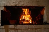 Red and orange crackling fire in russian wood stove poster