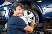 Confident Mechanic Fixing Alloy To Tire poster