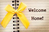 The words Welcome Home written on a old brown diary paper next to a yellow ribbonin reference to military returning from overseas duty. poster