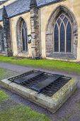 An iron cage (known as a mortsafe) covering a grave in Greyfriars Cemetery in Edinburgh Scotland. Mortsafes were used in the 19th century to prevent bodysnatchers from stealing corpes. poster
