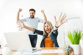 Cute two colleagues are celebrating their success. They are looking at laptop with satisfaction and raising arms up happily. Man and woman are smiling poster