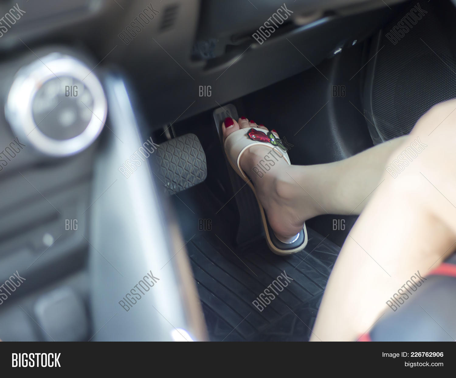 Selective Focus Of Female Foot With Red Nail Color Pushing On Pedal Car