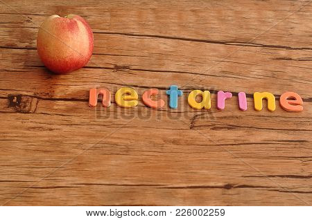 A Nectarine With The Word Nectarine On A Wooden Table