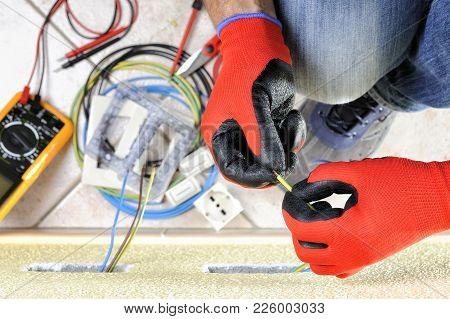 Electrician Technician At Work Prepares The Cable With Hands Protected By Gloves In A Residential El