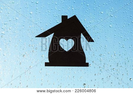 Home Sweet Home. Home Symbol With A Heart Shape On A Window Background With Sunny Drops Of Rain.