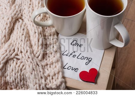 One Long Life Of Love Is An Abstract Symbolic Image. Couple Of Cups, Background Warm Scarf, In Home
