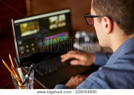 Freelancer Video Editor Works At The Laptop Computer With Movie Editing Sofware. Videographer Vlogge