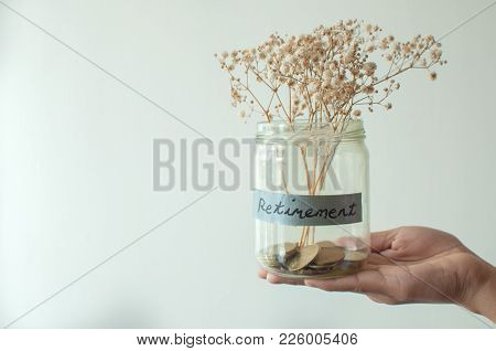 A Hopeless Retirement Concept Jar With Coins And Dried Plant