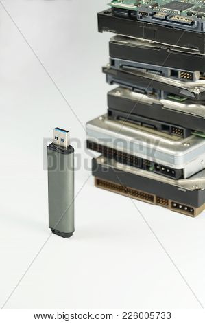 Pendrive And Stack Of Classic Hard Drives In The Background