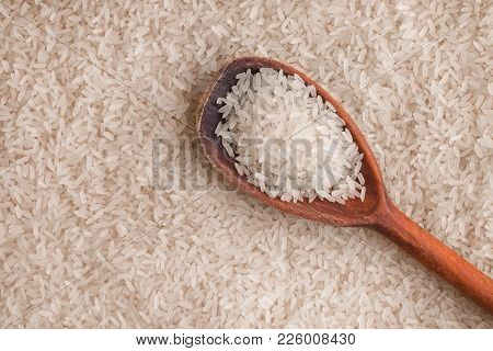 White Rice And A Wooden Spoon. A Wooden Spoon Filled With Rice Lies On The Rice.