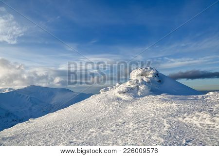 High Mountains And Blue Sky. Mysterious Fantastic Rocks Frozen With Ice And Snow Of Strange Fairytal