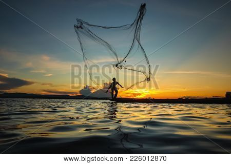 Asia Fisherman Throwing Net At Sunset In The River.