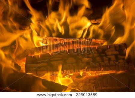 Burning Firewood Coal Closeup In The Fireplace. Fire Fireplace Ember Wood Home Embers Closeup. Glowi