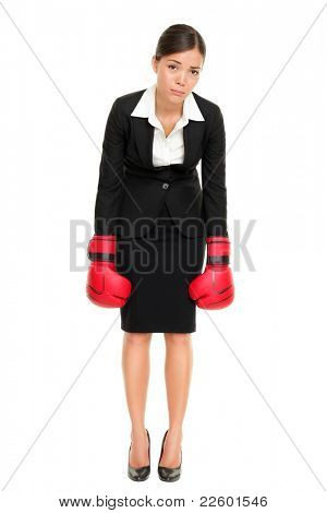 Defeated loser woman - business concept with businesswoman wearing boxing gloves standing in full body looking hopeless. Young Asian / Caucasian female professional isolated on white background.
