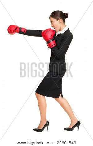 Business woman boxing - business competition concept with businesswoman punching and hitting standing in full length profile. Young Asian / Caucasian female professional isolated on white background.
