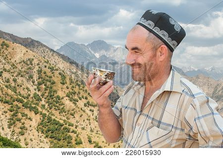 Portrait Of A Tajik Man In Skullcap With A Cup Of Tea On The Background Of The Hissar Range