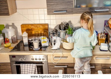 Little Girl Baking Waffles In The Kitchen At Home Following A Recipe On The Smartphone While Standin