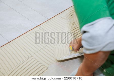 Worker Installs Tiles On The Floor. He Put Glue Using Comb Trowel. Master Puts Adhesive