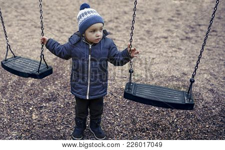 Adorable Little 2-3 Year Old Boy Having Fun On Playground, Child Wearing Blue Hoody Jacket And Blue