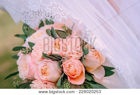 Bouquet Of The Bride Pink Flowers Green Eucalyptus On The Background Of A Wedding Dress