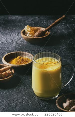 Cup Of Ayurvedic Drink Golden Milk Turmeric Latte With Curcuma Powder And Ingredients Above Over Bla